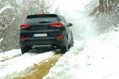 在泥和雪的越野SUV 库存图片
