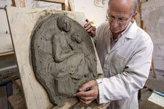 在泥塑的艺术家姿态在艺术演播室 免版税库存图片