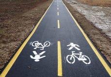 在泥泞的冬天乡下之间的平直的沥青自行车车道 免版税库存照片