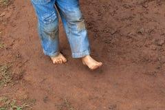 在泥泞的地面的孩子肮脏的脚 免版税库存照片