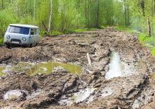 在泥泞的森林公路困住的汽车 免版税库存图片