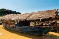 在泥泞的河的木小船 免版税库存照片