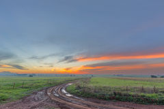 在泥泞的路的日落 免版税库存图片