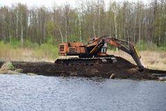 在泥炭沼的老被放弃的挖掘机在水中间 图库摄影