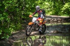 在泥的Enduro moto与大飞溅 免版税图库摄影