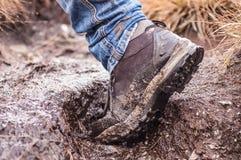 在泥盖的一双远足的鞋子的侧视图 免版税库存图片