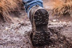 在泥盖的一双远足的鞋子的脚底 免版税库存照片