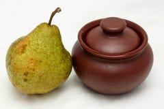 在泥罐旁边的大绿色梨 免版税库存图片