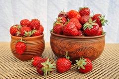 在泥罐的草莓在桌上 免版税图库摄影