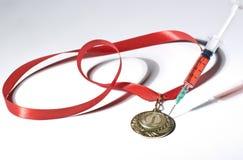 在注射器的普遍的红色类固醇作为掺杂刺中在白色背景的一枚金牌 免版税库存照片