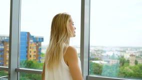在注视着窗口的快乐的白肤金发的妇女外面的徒升都市风景 影视素材