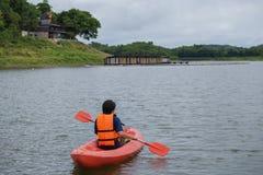在泰国供以人员用浆划在一条皮船小船 免版税库存照片