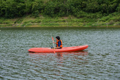 在泰国供以人员用浆划在一条皮船小船 免版税库存图片