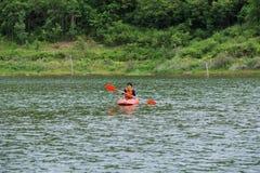 在泰国供以人员用浆划在一条皮船小船 库存照片