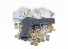 在泰国金钱钞票和硬币的手枪 免版税库存图片