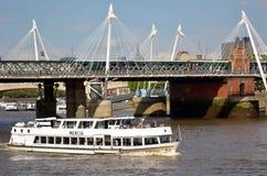在泰晤士河巡航的乘客服务在Hungerford桥梁下 免版税库存照片