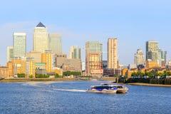 在泰晤士河的一条巡航的小船和backgro的金丝雀码头 图库摄影
