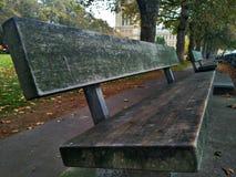 在泰晤士河的银行的一个长木凳 伦敦,大英国 免版税库存照片