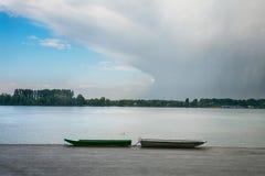 在泽蒙奎伊Zemunski kej的两个渔船在多瑙河,贝尔格莱德,塞尔维亚首都的一个多云下午 库存图片