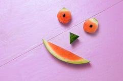 在洋红色背景的微笑的西瓜 库存图片