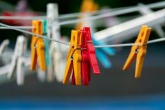 在洗涤的线的红色和黄色晒衣夹 免版税库存照片