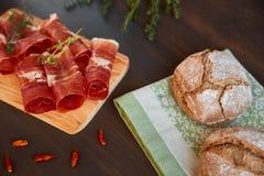 在洗碗布的新近地被烘烤的手工制造面包 新鲜的绿色麝香草和热的红辣椒 在一个木板的Succulend烟肉 库存图片