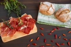 在洗碗布的新近地被烘烤的手工制造面包 新鲜的绿色麝香草和热的红辣椒 在一个木板的Succulend烟肉 免版税库存图片