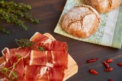 在洗碗布的新近地被烘烤的手工制造面包 新鲜的绿色麝香草和热的红辣椒 在一个木板的Succulend烟肉 图库摄影