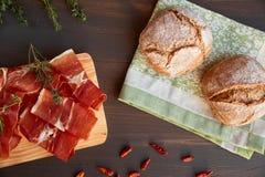 在洗碗布的新近地被烘烤的手工制造面包 新鲜的绿色麝香草和热的红辣椒 在一个木板的Succulend烟肉 免版税图库摄影
