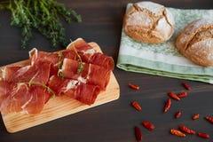 在洗碗布的新近地被烘烤的手工制造面包 新鲜的绿色麝香草和热的红辣椒 在一个木板的Succulend烟肉 免版税库存照片