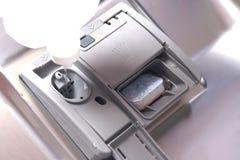 在洗碗机的金属门,有洗涤剂里面的灰色塑胶容器和玻璃调节剂倾吐 库存图片