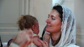 在洗礼期间,教士剪从婴儿` s头的第一根头发 影视素材