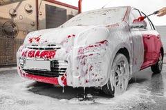 在洗车的起泡沫的红色汽车 库存照片