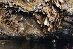 在洞里面的石纹理和划船妇女在的Trang荡桨有游人的一条小船洞穴在Ninh Binh,越南 免版税库存照片