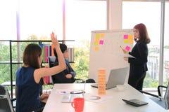 在活动挂图的年轻亚洲女商人介绍对同事在会议期间在会议室 免版税图库摄影