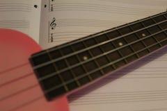 在活页乐谱的桃红色尤克里里琴 免版税库存图片