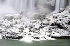 在流动入光滑的aqu的大瀑布下的积雪的岩石 免版税库存照片