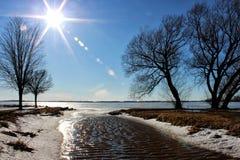 在流动入冻湖的入口的太阳 免版税库存照片
