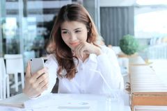在流动巧妙的电话的选择聚焦在相当在selfie之间的亚裔妇女的手上在商店弄脏了背景或拍一张照片 库存图片