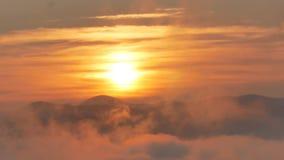 在流动的云彩上的精采山顶黎明挥动,红色太阳盘 股票视频