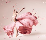 在流动的桃红色礼服的芭蕾舞女演员跳舞有飞行瓣的 免版税库存图片