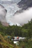 在流游人的桥梁briksdal冰川 免版税图库摄影