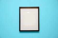 在浅兰的墙壁上的空白的黑框架 库存图片