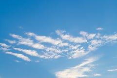在浅兰的夏季的天空的白色fkuffy多云线 免版税库存图片
