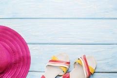 在浅兰的背景和一个桃红色帽子的明亮的夏天鞋子 免版税库存图片