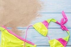在浅兰的背景的明亮的比基尼泳装 库存图片