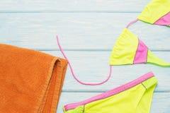 在浅兰的背景的明亮的比基尼泳装 免版税库存照片