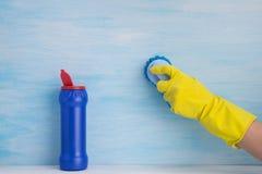 在浅兰的背景,在一副黄色橡胶手套的一只手,在它旁边掠过表面,是有清洁的一个开放蓝色瓶 免版税图库摄影