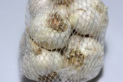 在浅灰色的背景隔绝的白色塑料网的白色大蒜 图库摄影