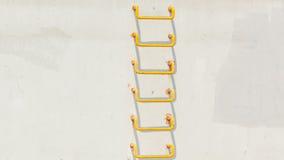 在浅灰色的conrecete墙壁上的黄色梯子 免版税库存照片